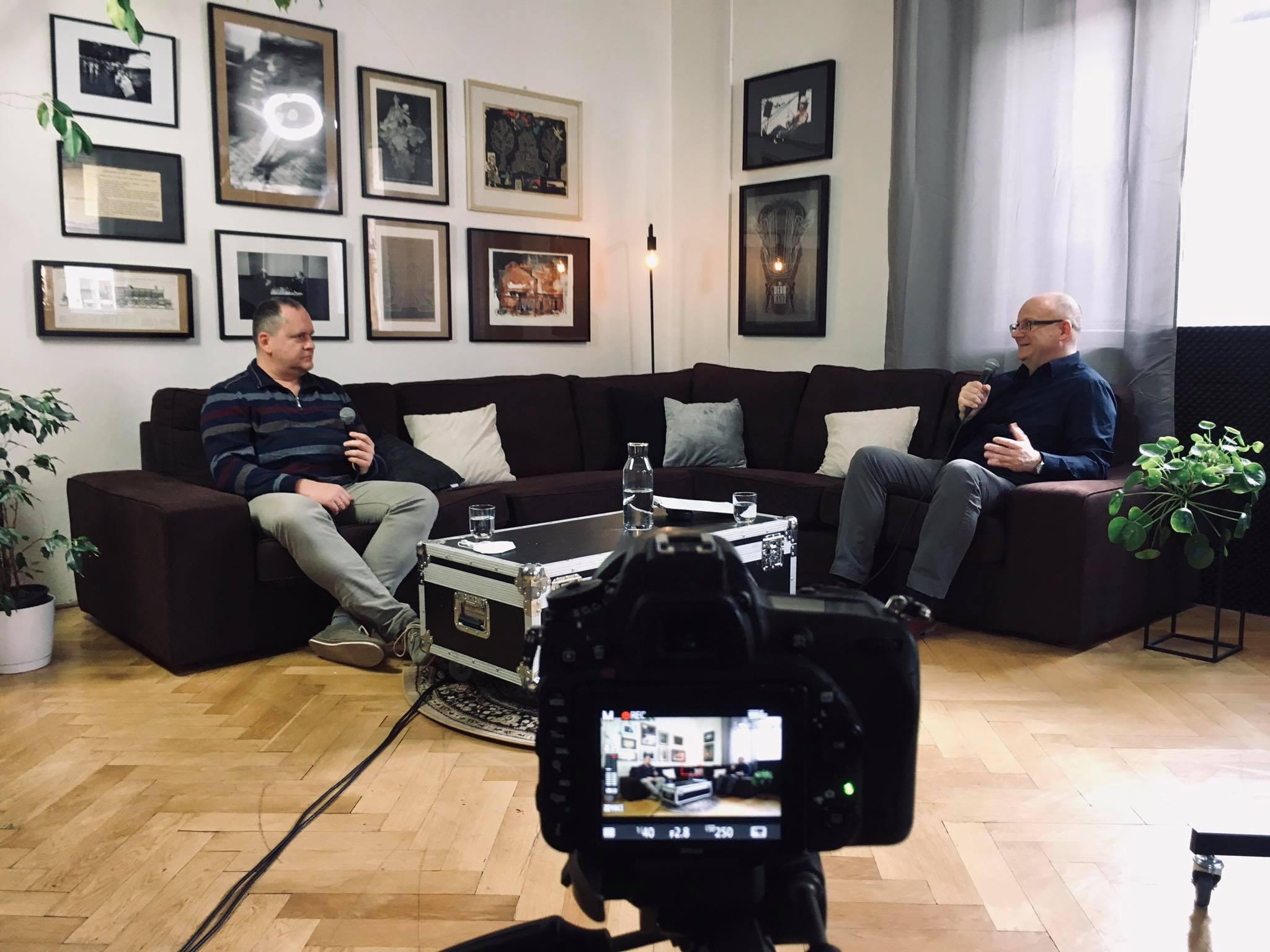 Branislav Moťovský a Ivan Ježík sediaci na gauči počas rozhovoru, v popredí fotoaparát