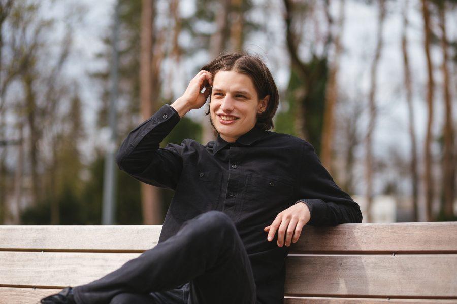 Samo sedí na lavičke, usmieva sa a škrabe sa nad uchom