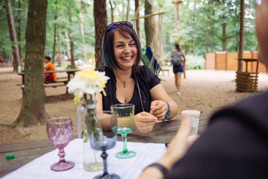 Smejúca sa Janka, v popredí stôl s kyticou a pohármi, v pozadí ľudia v parku