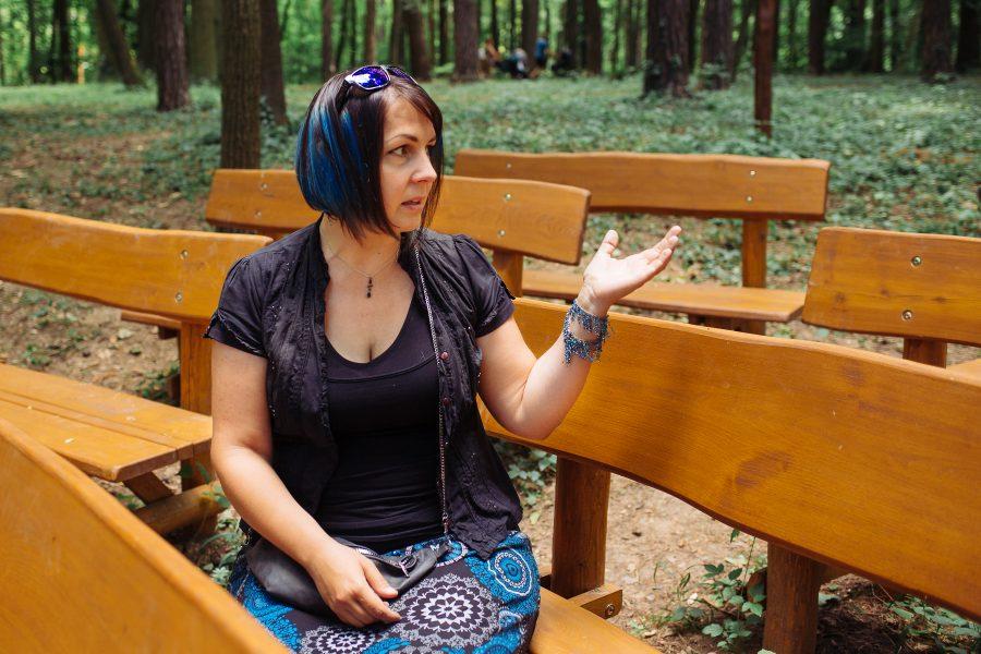 Janka sedí na lavičke a rukou ukazuje okolo seba