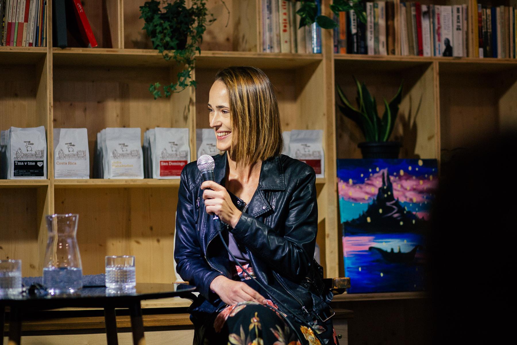 Magda Frecer počas rozhovoru, v pozadí knižnica a obrazy