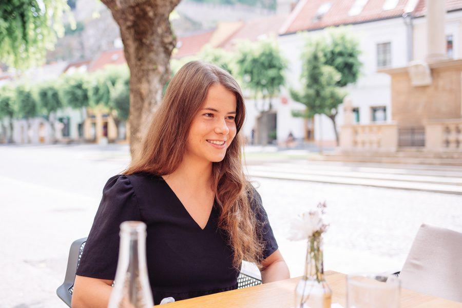 Terka sediaca za stolom na terase a usmievajúca sa