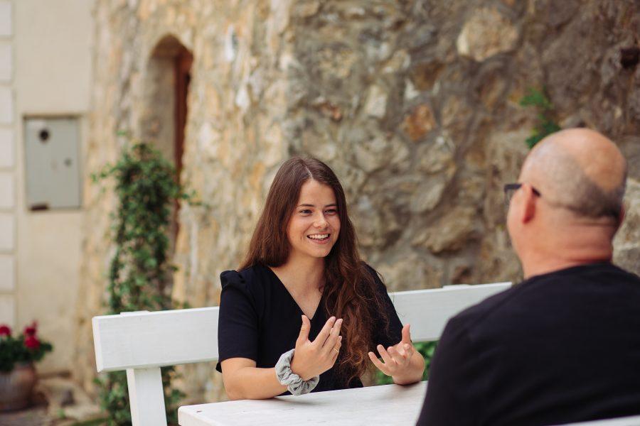 Terka počas rozhovoru s Ivanom, sedí na bielej lavičke a gestikuluje rukami