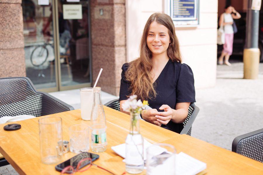 Terka s úsmevom sediaca na terase kaviarne